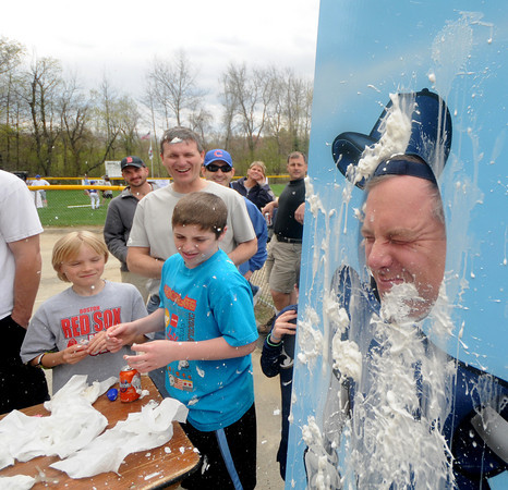 Byfield: Coach Tim Perry gets face full of whipped cream thrown by some of his players at opening day at the Byfield Little League Saturday. Jim Vaiknoras/Staff photo