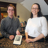 Newburyport: Newburyport Library workers Colin Powell and Jane Lemuth pose with a Kindle at the library. Libray books will soon be available for the digital reading device. Jim Vaiknoras/Staff photo