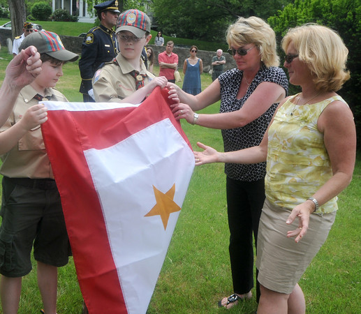 Newburyport: Susan Hines and Holly Shay, whose sons Derek and Jordan were killed in the line of duty, present a Gold Star Mother's flag to scouts Ryan Hankins and Samual Lewis at Veteran's Cemetary in Newburyport at the close of the Memorial Day service Monday. Jim Vaiknoras/Staff photo