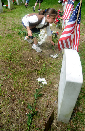 Newburyport: Lily Salka, 9, of troop 63168 places carnations on the graves of veterans at Veteran's Cemetary in Newburyport at the close of the Memorial Day service Monday. Jim Vaiknoras/Staff photo
