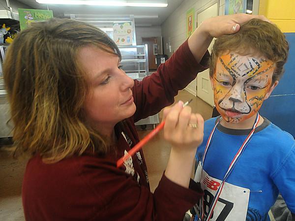 Newburyport:Will Pflaum, 5, gets a tiger painted on his face by Danielle Gallagher at the Newburyport Elementary PTO6th Annual  Spring Fever 5K &<br /> Family Fun Run at the Bresnahan School in Newburyport Sunday. the fundraiser included a 5k roadrace as well as a family fun run. Jim Vaiknoras/Staff photo
