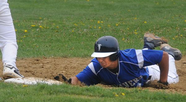 Peabody: Danvers' Mike Valles kicks up some dirt as he dives safely back to first during the Falcons game at Bishop Fenwich Sunday. Jim Vaiknoras/staff photo