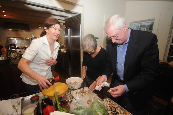 Newburyport Kathy Bechtel works with Tom O'Neil amd Laurie Christiansen during her cooking class at her home in Newburyport. Jim Vaiknoras/Staff photo