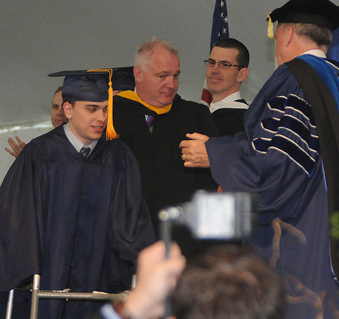 Danvers: Jared Coppola, who was injured playing football his sophmore year, walks across the stage to get his diploma at St John's commencement Sunday morning. Jared will be attending UNH in the fall, Jim Vaiknoras/Staff photo