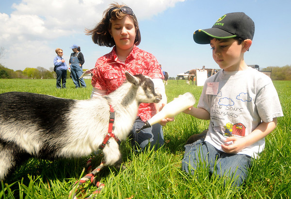Newbury: Hannah Knittling , 13, and Alex Yablin, 6, feeds Appleton, a resently rescued 6 week old dwarf goat at the Draft Plow competition at the Spencer Pierce Little Farm Saturday. Jim Vaiknoras/Staff photo