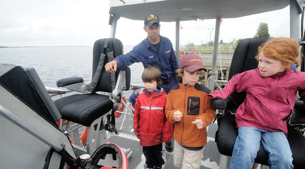 Newburyport: Seaman Michael Aptacy shows Kellen McDermott, 6, his brotehr Cameron, 9, and his sister Carly, 5, around the bridge of the 44 footer at the Coast Guard Station Open house Sunday. Jim Vaiknoras/Staff photo