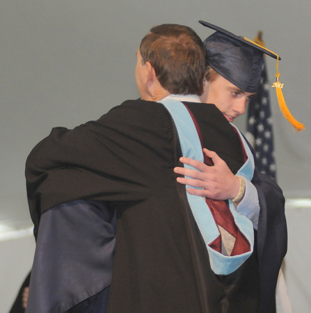 Danvers: St John's Prep graduate Matthew Chelsey gets a hug from his father Glen, who is on the faculty at the school,at commencement Sunday morning. Jim Vaiknoras/Staff photo