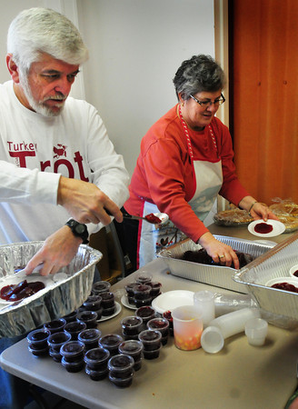 Newburyport: Mike and Sue Coppinger man the cranberry sauce station at the Salvation Army headquarters in Newburyport yesterday morning. They were among the couple dozen volunteers helping the Lion's Club with their annual Thanksgiving Dinner. Bryan Eaton/Staff Photo