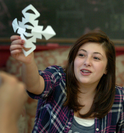 Newburyport: Lori Giunta, 13, shows one of the snowflakes she cut out at the Kelley School Teen Center on Monday afternoon. She was on one of two teams to see who could make the most snowflakes to decorate the building, the winning team winning prizes. Bryan Eaton/ Staff Photo