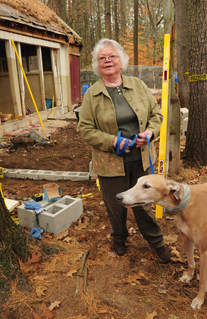 Salisbury: Marilyn Wolkovits with her greyhound, Levi, look over renovation of her kennel that will house other greyhounds taken from dogtracks, later to be adopted. Bryan Eaton/Staff Photo