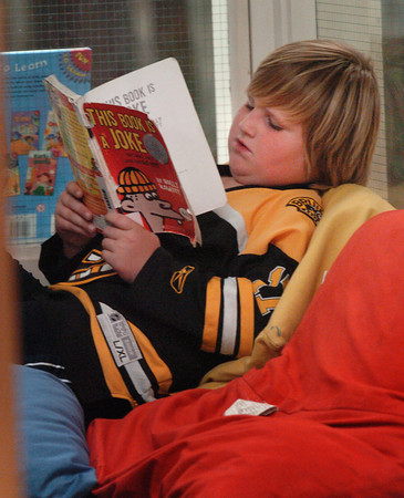 """Amesbury: Devin Gannon, 8, settles down with """"This Book is a Joke"""" in the reading loft at the library at Amesbury Elementary School. Students once a week choose a couple books to take home, and if they have time, they start reading them in the cozy spot. Bryan Eaton/Staff Photo"""