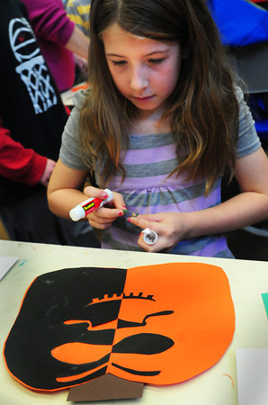 """Amesbury: Kristin Litzenberg, 8, creates a jack-o-lantern in Linda Greenfield's art class at the Cashman School in Amesbury on Monday. They  were learning about symmetric balance making one half of the image """"negative"""" and the other, """"positive."""" Bryan Eaton/Staff Photo"""