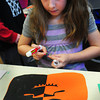 "Amesbury: Kristin Litzenberg, 8, creates a jack-o-lantern in Linda Greenfield's art class at the Cashman School in Amesbury on Monday. They  were learning about symmetric balance making one half of the image ""negative"" and the other, ""positive."" Bryan Eaton/Staff Photo"