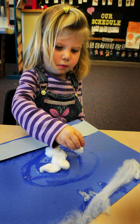 Newbury: Julia Blanchet, 3, glues different shapes of cotton onto blue paper in Mary Jo Lagana's preschool class at Newbury Elementary School on Tuesday. The different pieces of cotton represented different clouds the youngsters are learning about, stratus, cirrus and cumulus. Bryan Eaton/Staff Photo
