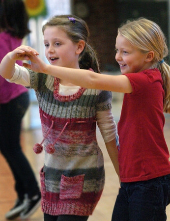 Newburyport: Hannah Cronin, left, and Ellie Turgeon, both 8, learn the Turkey Tango in physical education class at the Bresnahan School on Monday afternoon. They were learning different dances with a Thanksgiving theme including an American Indian dance. Bryan Eaton/Staff Photo