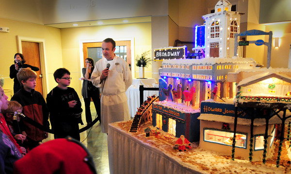 Salisbury: Seaglass restaurant bartender James Shalkoski answers questions from children at the Boys and Girls Club at the lighting of a giant gingerbread display in the lobby of the Pavillion. The display of buildings of Salisbury Beach past took him 100 hours to make. Bryan Eaton/Staff Photo
