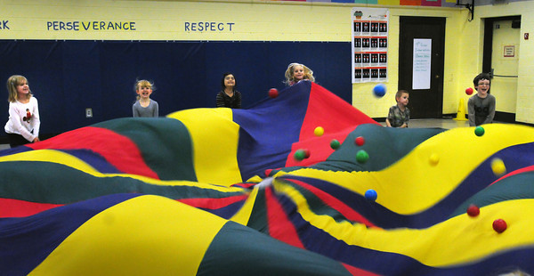 """Amesbury: Students pull a parachute up and down trying to move all fifty plastic balls off it in a game of """"popcorn"""" Wednesday afternoon. They were in Margaret Welch's physical education class at the Amesbury Elementary School. Bryan Eaton/Staff Photo"""