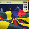 "Amesbury: Students pull a parachute up and down trying to move all fifty plastic balls off it in a game of ""popcorn"" Wednesday afternoon. They were in Margaret Welch's physical education class at the Amesbury Elementary School. Bryan Eaton/Staff Photo"