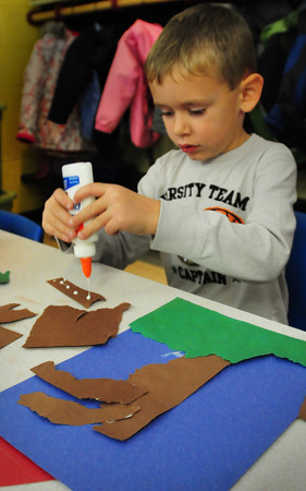 "Amesbury: Sam Guimaraes, 5, squirts drops of glue to one of the ""branches"" he's putting together on a tree, before adding pieces of orange paper for leaves. He was at Amesbury Elementary School in Rebecca Reeses class on Thursday morning. Bryan Eaton/Staff Photo"