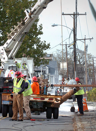 Newburyport: An electric crew from Michigan, diverted from storm-related work in New Hampshire, replace a telephone pole on Water Street yesterday afternoon. The pole was hit by an alledged drunk driver early in the morning cutting power to the area. Bryan Eaton/Staff Photo