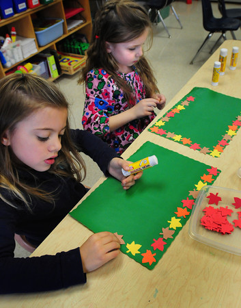 Newburyport: Avery LaBua, left, and Gabby Hanson, both 5, work dinner placement mats in Melissa Duguie's kindergarten class at the Brown School in Newburyport on Monday. They're making the pieces for their Thanksgiving Dinner next Tuesday. Bryan Eaton/Staff Photo