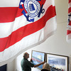 Newburyport: Norm Hansen, assistant curator of the Custom House Maritime Museum, left, and curator Caroleann McPherson hang paintings from different artists of the life of the US Coast Guard for an exhibit for Yankee Homecoming.<br /> Bryan Eaton/File Photo