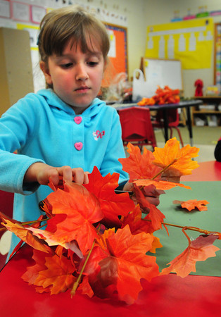 "Newburyport: Abigail Ryan, 6, cuts out synthetic leaves to create a piece of artwork in Talia Hallett's first grade class at the Bresnahan School in Newburyport on Monday afternoon. The children were learning about trees and read the book ""Leaf Man."" Bryan Eaton/Staff Photo"
