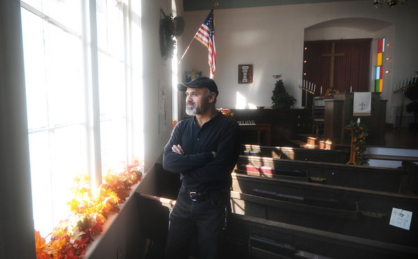 Amesbury: Paul Prue of Bradford, looks over the window that he will be replacing at Union Congregational Church in Amesbury. Jim Vaiknoras/staff photo