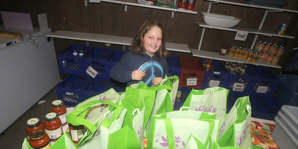 Amesbury: Shannon Cote, 9, empties 16 shopping bags full of food at Our Neighbors Table in Amesbury Saturday. In lue of  presents she took all of her birthday money , shopped for the food and donated it to the charity. Shannon is a student at the Immaculate Conception school in Newburyport. Jim Vaiknoras/staff photo