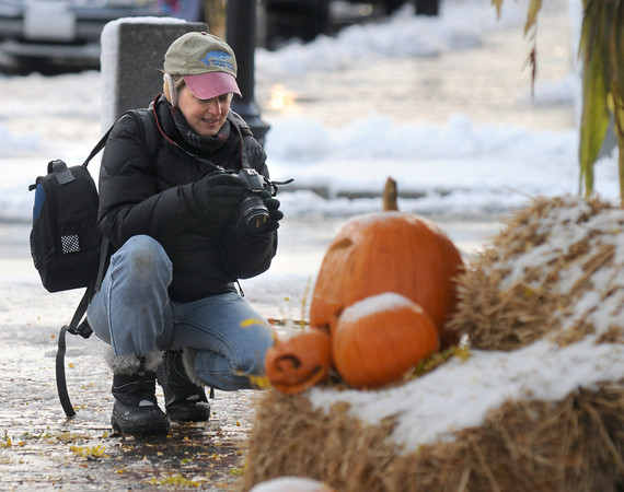 Newburyport: Photographer Suzanne Degeorge was all bundled up as she shoots photos of snow on pumpkins in Market Square in Newburyport Sunday morning. Jim Vaiknoras/staff photo
