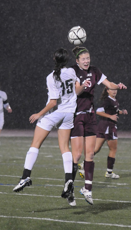 Lynn: Newburyport's Hannah Martin goes up for a header with Canton's Kim McNally during the Clippers 3-0 loss to Canton in the state semi-final game at Manning Field in Lynn. JIm Vaiknoras/staff photo