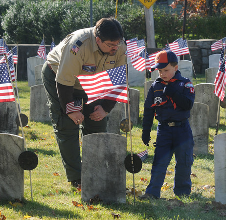 Newburyport: Tim Conway and his son Desmond, 6 read the names of Veterans on grave markers in Veteran's Cemetary Friday morning. Desmonds scout troop, Troop 21, marched in the annual parade.  Jim Vaiknoras/Staff photo