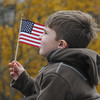 Amesbury: Owen Simas, 5, hold the flagas he sits on his father Jim's shoulders during the playing of the National Anthem at the Veteran's Day service at Amesbury Middle School. Jim Vaiknoras/staff photo