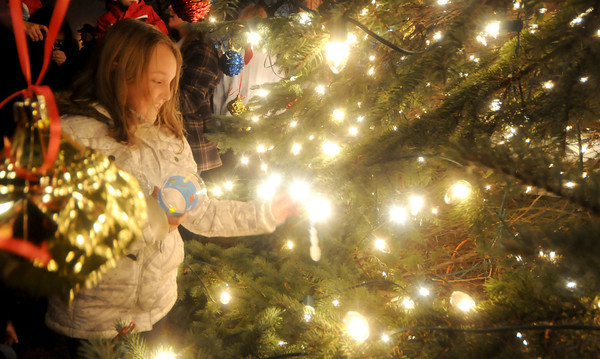 Salisbury Madisyn Weldon, 9, a 3rd grader at Salisbury Elementary School, puts an ornament on the newly lit Christmas Tree in Salisbury Square Sunday night. staff photo