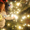 Salisbury Madisyn Weldon, 9, a 3rd grader at Salisbury Elementary School, puts an ornament on the newly lit Christmas Tree in Salisbury Square Sunday night. staff photo