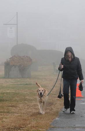 Newburyport: Donna Pierce walks her dog Charlie through the fog along the seawall in Joppa Park in Newburyport Thursday afternoon. Jim Vaiknoras/staff photo