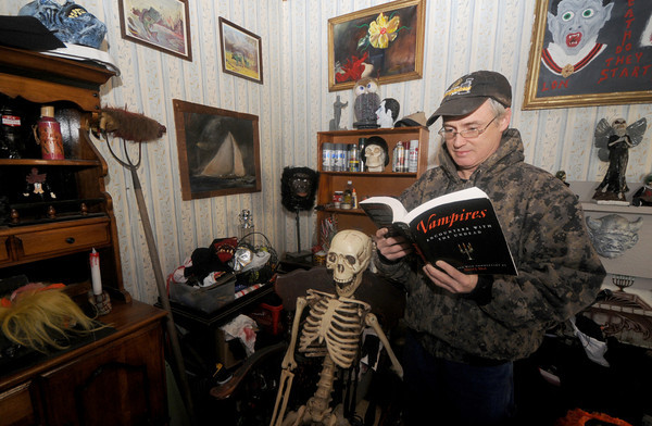 Newburyport: John Hewett has gone all out decorating his Munroe Street home in Newburyport  for Halloween. Here he reads to one of his visitors Jim Vaiknoras/staff photo