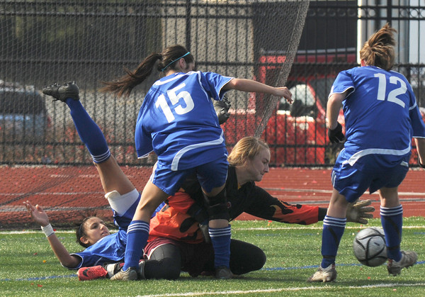 Lynn: Newburyport Lilly Donavan makes a save amonst a trio of Stoneham's players during the Clipper victory in the North sectional final at Manning Field in Lynn Saturday. Jim Vaiknoras/staff photo