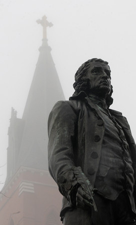 Amesbury: The steeple of the Holy Family Church in Amesbury looms in the fog behind the staue of Josiah Bartlett on School Street in Amesbury. Jim Vaiknoras/staff photo