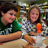 Newbury: Jeffrey Krisao, 10, left, and Elsa Comparone-Barre, 9, react as a balloon inflates ovn a beaker as antacid was dropped in to water before attaching the balloon at Newbury Elementary School on Tuesday. They were in Carol Towne's class learning about different states of matter and how a liquid and solid mixed together could create a gas. Bryan Eaton/Staff Photo