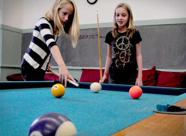 Newburyport: With rain outside, Ava Gridley, left, and Emma Fisher, both 11, play a game of pool at the Kelley School Teen Center on Thursday. They were sure who was winning since they were just learning to play. Bryan Eaton/Staff Photo