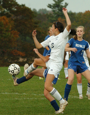 Byfield: Triton's Shannon Dube clashes with Georgetown players yesterday in Byfield. Bryan Eaton/Staff Photo