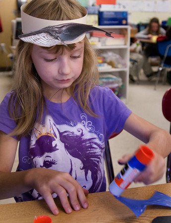 Amesbury: Nicole LaFlamme, 7, works on a project making a Halloween cat while wearing a headband sporting a whale on it at Amesbury Elementary School. The students in Cathy Patten's class were learning about marine mammals. Bryan Eaton/Staff Photo