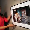 "Newburyport: Lily Ackerly of the Newburyport Art Association hangs the lastet Best of Show, a photograph entitled ""Modern Kitchen"" by Al Hiltz of Medford. Bryan Eaton/Staff Photo"