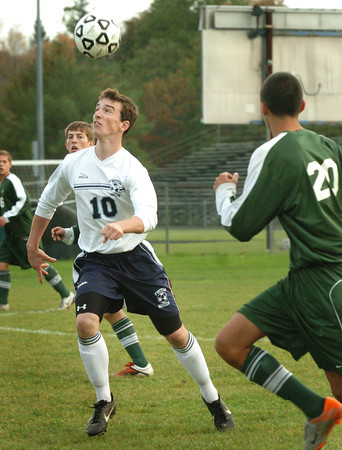 Byfield: Triton's Jake Stelline heads the ball away from North Reading defenders. Bryan Eaton/Staff Photo