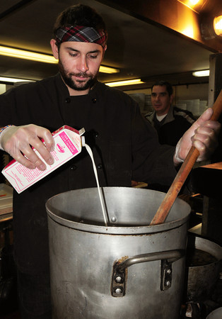 Newburyport: Patrick Abenante of the Starboard Galley adds cream to enrich their Southwest Chicken and Corn Chowder for Saturday's Chowder Festival. Bryan Eaton/Staff Photo