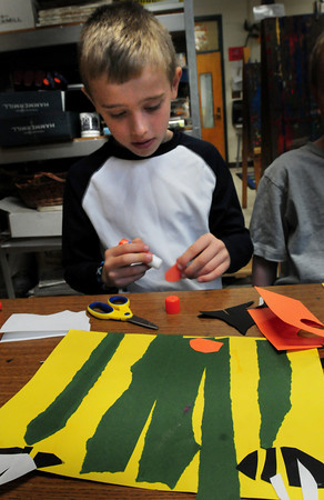 """Newburyport: Andrew Orem, 7, glues pieces of a catterpillar in Pam Jamison's art class at Bresnahan School in Newburyport. They were creating  scene from the book they read """"The Tall, Tall Grass."""" Bryan Eaton/Staff Photo"""