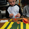 "Newburyport: Andrew Orem, 7, glues pieces of a catterpillar in Pam Jamison's art class at Bresnahan School in Newburyport. They were creating  scene from the book they read ""The Tall, Tall Grass."" Bryan Eaton/Staff Photo"