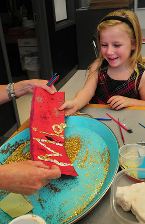 Salisbury: First-graders in Shannon O'Brien's art class at Salisbury Elementary School created their names with clay. Mia Orsillo, 6, smiles as the teacher shakes off golden glitter on her artwork. Bryan Eaton/Staff Photo