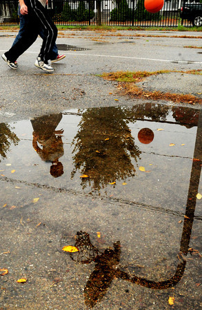 Newburyport: Twins Brian and Nick Toolan, and friend Elias Camponella-Garcia, all 12, play some basketball at the Kelley School Playground reflected in on of several puddles there. Rain continues today with clearing for the weekend. Bryan Eaton/Staff Photo